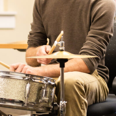 A student plays a drum kit